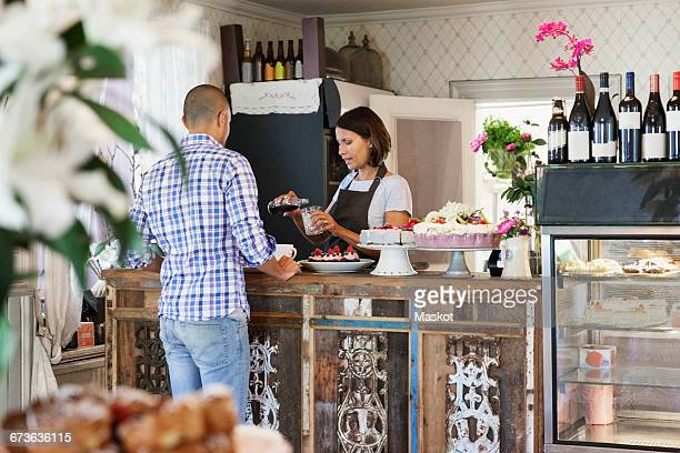 Female owner serving drink in glass for customer at counter in cafe