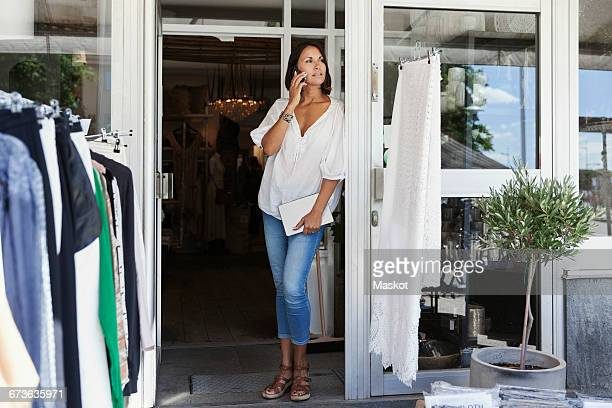 Female owner talking on phone while standing at entrance of clothing store