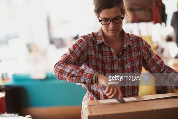 female owner unpacking box with utility knife at store - utility knife stock pictures, royalty-free photos & images