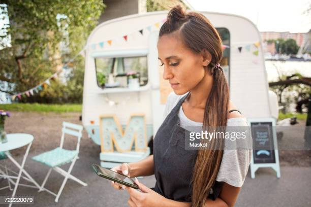 Female owner using mobile phone on street against food truck