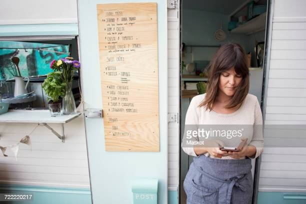 Female owner using smart phone outside food truck