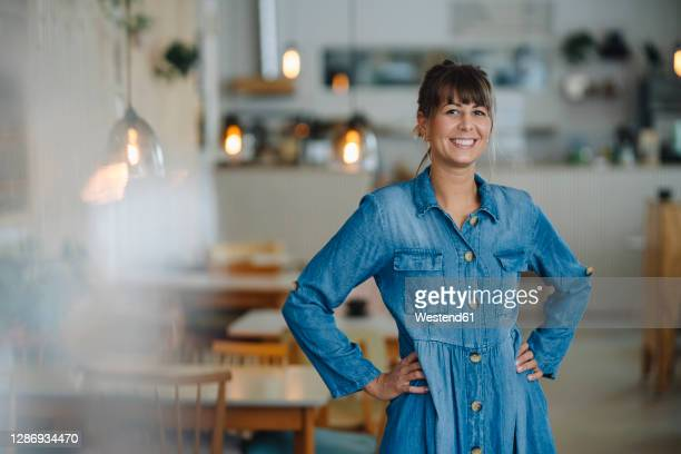 female owner with hand on hip standing in coffee shop - hand on hip stock pictures, royalty-free photos & images