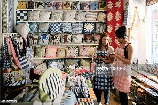 Female owners talking while holding smart phone and digital tablet in fabric shop