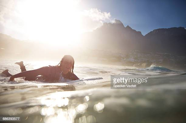 Female paddling in the ocean, at sunrise