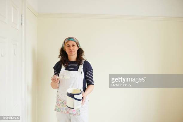 Female painter and decorator holding brush and paint can