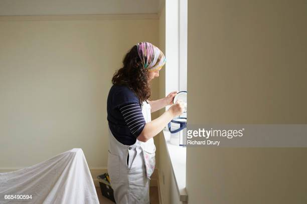 Female painter and decorator mixing paint