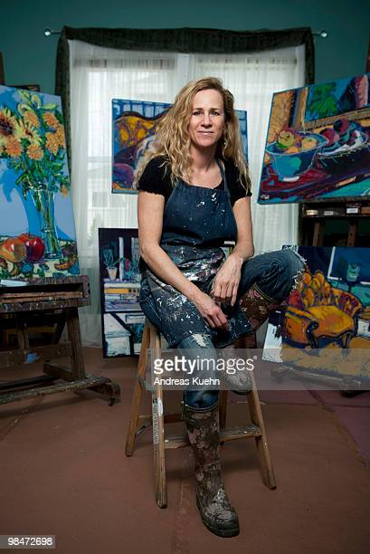 Female painter sitting in studio with her art.