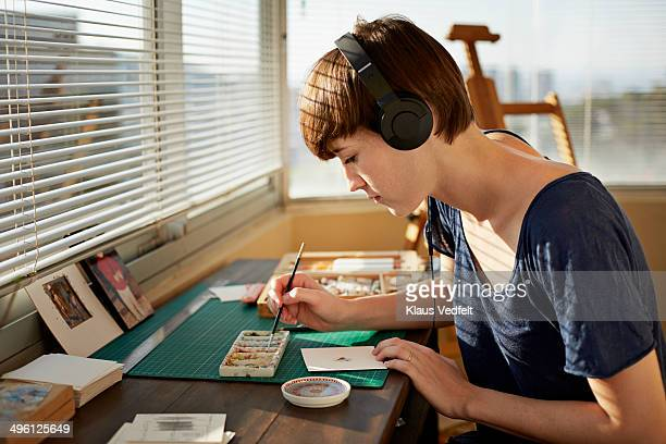 Female painter working at studio with headphones
