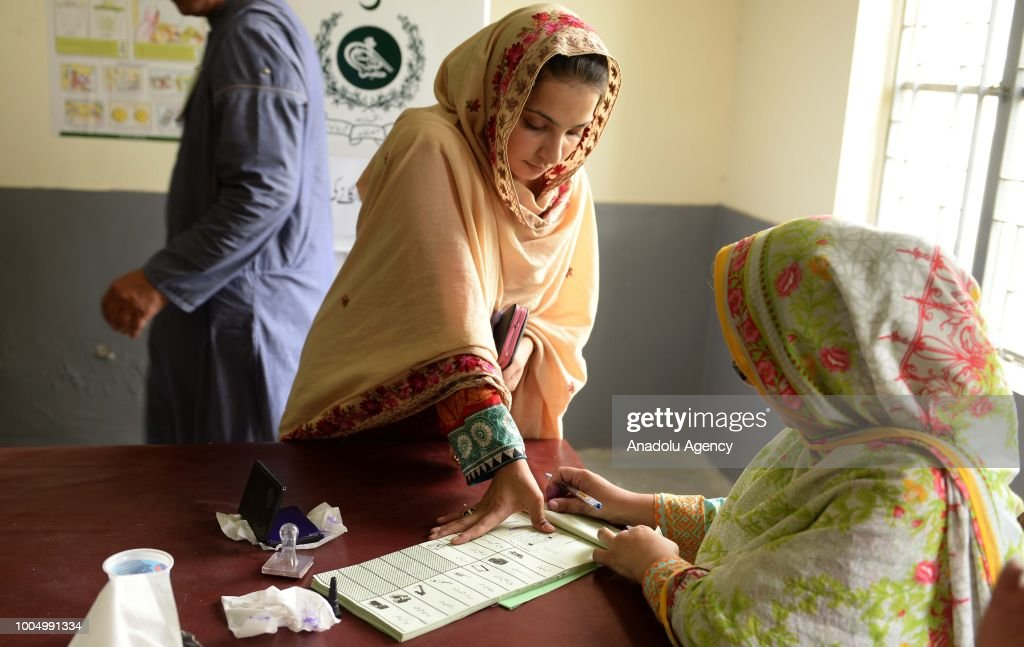 A female Pakistani polling official gets thumb impression from woman voter before allowing her to cast her vote at a polling station in Rawalpindi...