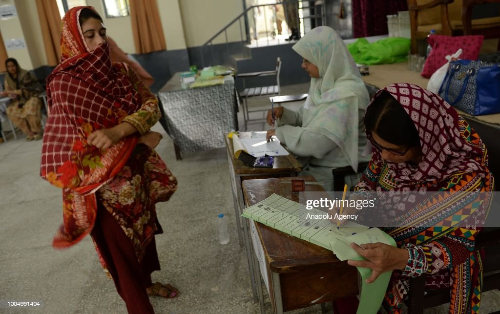 A female Pakistani voter waits to get her ballot paper from a polling official to cast her ballot at a polling station in Rawalpindi Pakistan on July.