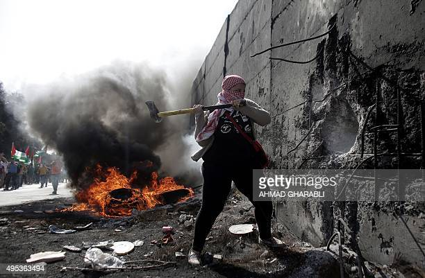 A female Palestinian demonstrater uses an axe to try and destroy a part of the Israeli controvertial separation wall separating the West Bank city of...