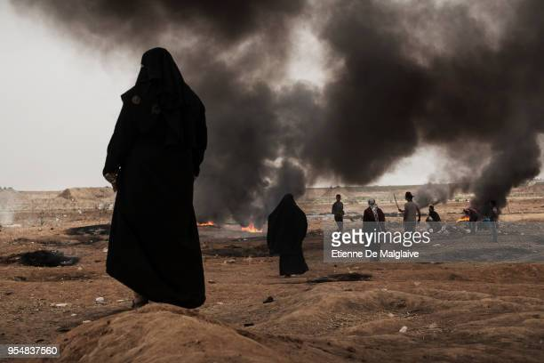 Female Palestinian protesters watch the border fence during clashes with Israeli forces on May 4, 2018 in Khan Yunis, Gaza. Israeli troops fired live...