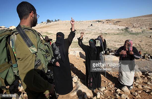 Female Palestinian shepards complain to an Israeli soldier after an Israeli settlers from the Maaon settlement harassesed them and their sheep near...