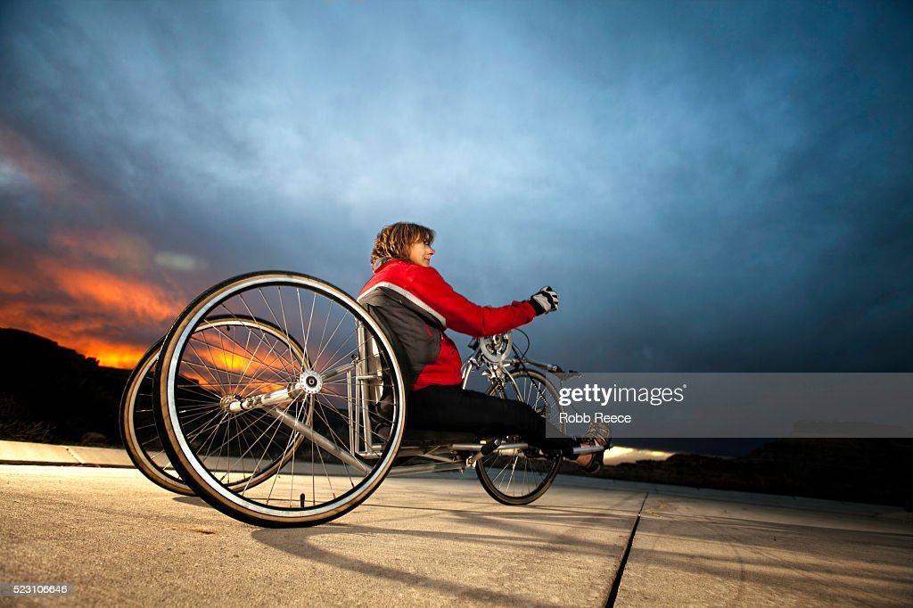 A female para-athlete rides her handcycle : Stock Photo