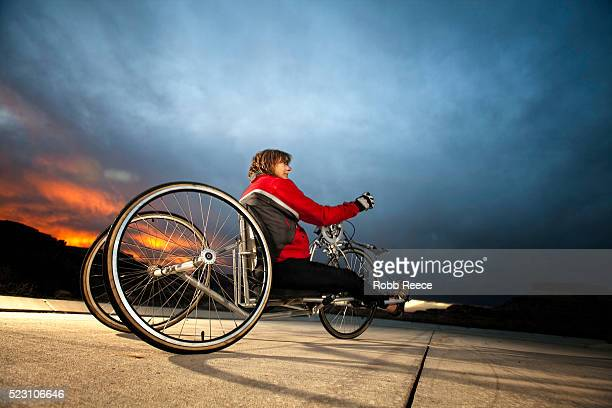 a female para-athlete rides her handcycle - robb reece stock photos and pictures