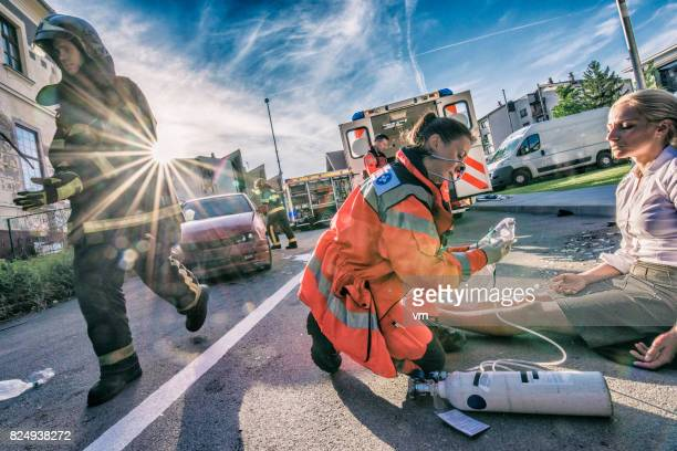 female paramedic helping injured woman - rescue services occupation stock photos and pictures