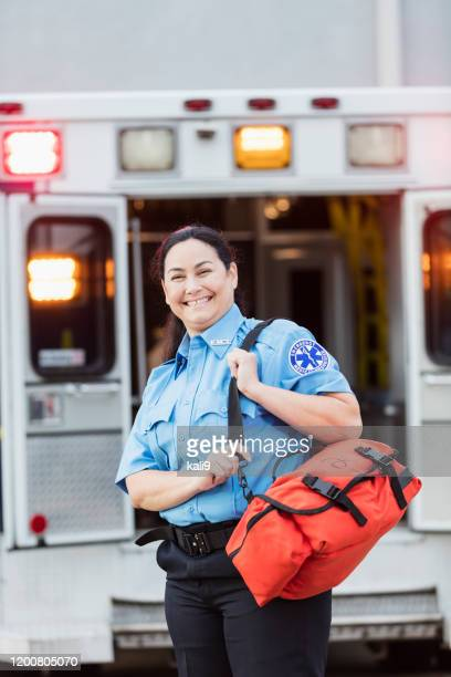 Female paramedic standing at the rear doors of an ambulance