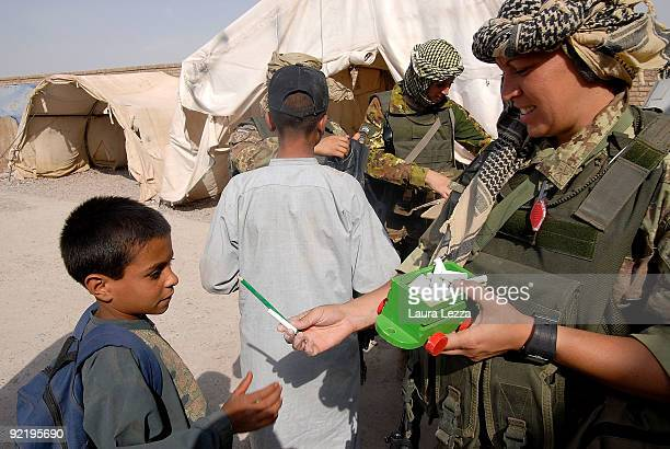 A female paratrooper soldier of the Folgore Parachute Brigade gives some pencils to an afghan child inside a children school on September 16 2009 in...