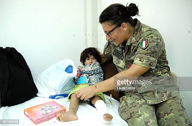 A female paratrooper soldier of the Folgore Parachute Brigade takes care of an injured afghan child in Camp Arena on September 21 2009 in Herat...