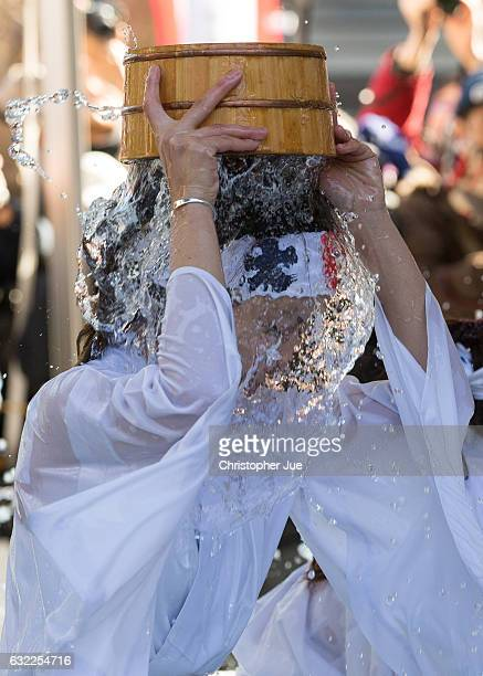 A female participant splashes icecold water on herself during the ice water winter purification ceremony on January 21 2017 in Tokyo Japan At Daikoku...