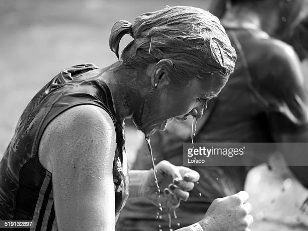 Female participant struggles at a mud run event