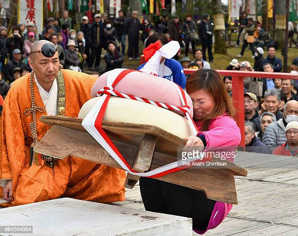 A female participant tries to lift 90kilogram rice cake during MochiAge 'rice cake lifting' as a part of GodaiRikison Ninnoe festival at Daigoji...
