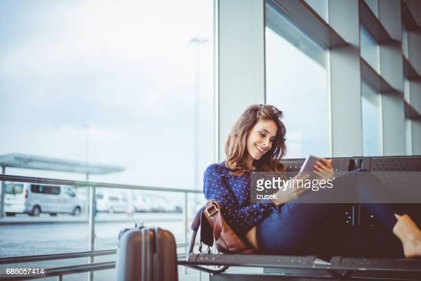 Female passenger at airport waiting area using digital tablet