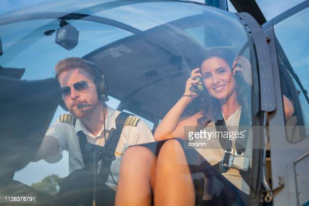 female passenger in helicopter cockpit by the  pilot adjusting headphones - helicopter photos stock pictures, royalty-free photos & images