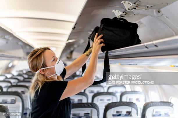 female passenger is wearing an ffp 3 face mask while putting luggage in lockers on plane - aeroplane stock pictures, royalty-free photos & images
