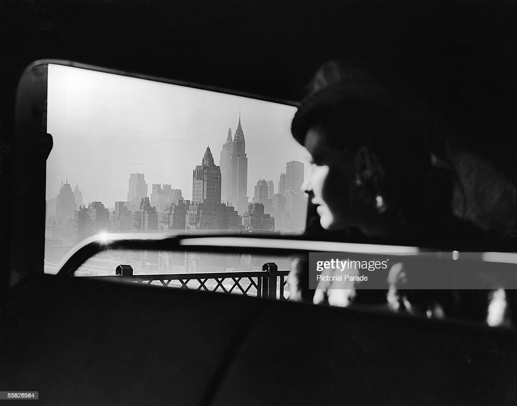 A female passenger on a bus which travels over the 59th Street Bridge to Queens looks out South onto the hazy New York City midtown skyline, New York, New York, 1940s. Prominant structures include the Daily News Building (left), Empire State Building (center, in the background) and the Chrysler Building (right).