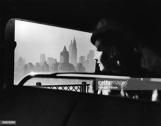 A female passenger on a bus which travels over the 59th Street Bridge to Queens looks out South onto the hazy New York City midtown skyline New York...