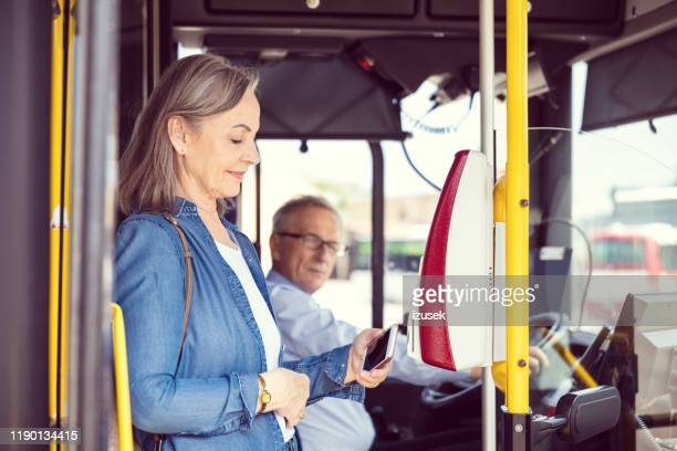 female passenger paying fare at entrance of bus - fare stock pictures, royalty-free photos & images