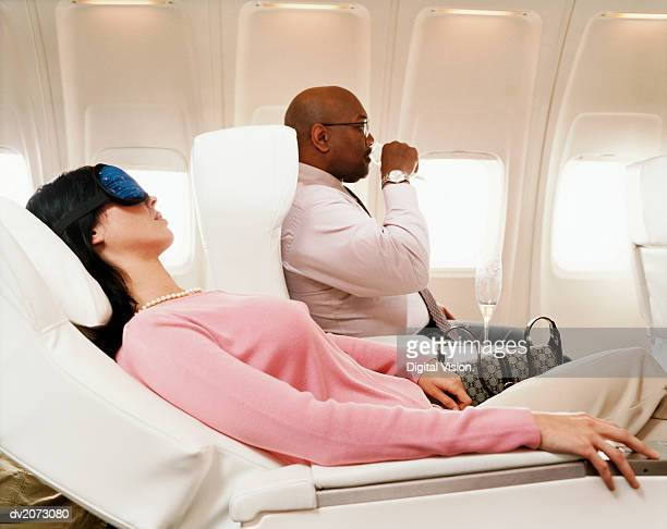 Female Passenger Sleeping and Man Drinking a Drink in an Aircraft Cabin Interior