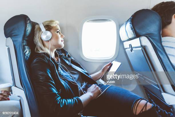 Female passenger using digital tablet during flight