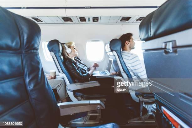 female passenger using laptop during flight - izusek stock pictures, royalty-free photos & images