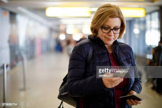 Female passenger using mobile phone in airport terminal