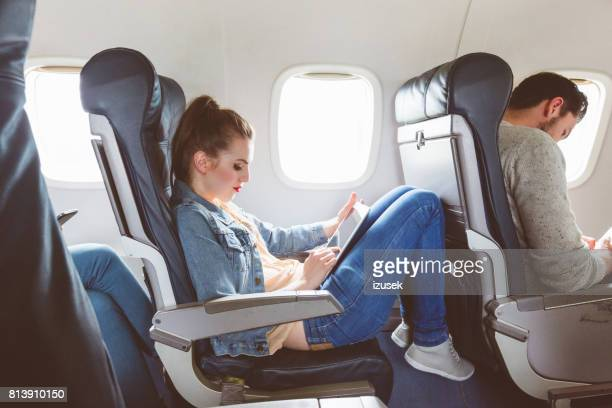 Female passenger using tablet pc during flight