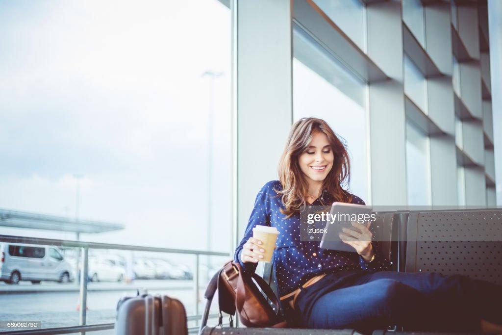 Female passenger waiting her flight at airport lounge : Stock Photo