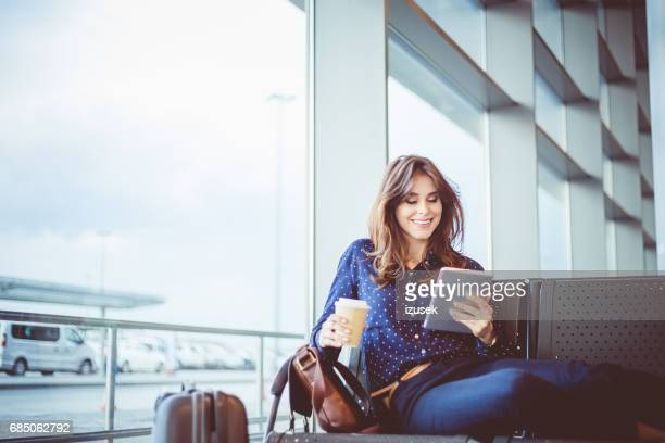 female passenger waiting her flight at airport lounge - passenger stock pictures, royalty-free photos & images