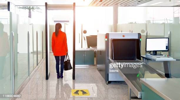 female passenger walking through the airport security checkpoint - security scanner stock pictures, royalty-free photos & images