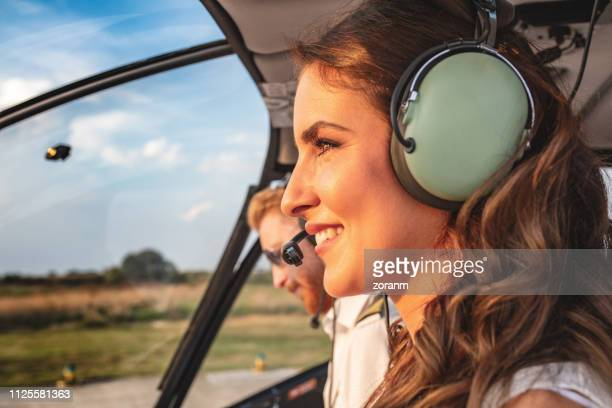 female passenger with headset in helicopter cockpit sitting by the pilot - inside helicopter stock pictures, royalty-free photos & images