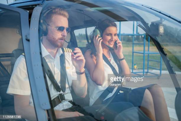 female passenger with headset sitting in helicopter cockpit with pilot, using phone - inside helicopter stock pictures, royalty-free photos & images