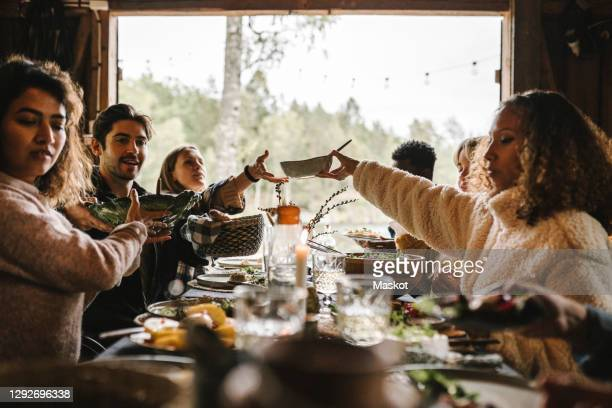 female passing food bowl to friend over table during social event - holiday stock pictures, royalty-free photos & images