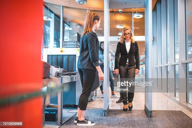 female passing through metal detector at airport - security scanner stock pictures, royalty-free photos & images