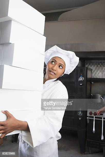 Female pastry chef carrying stack of boxes