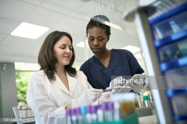 mujer patóloga y técnico examen de la prueba de tube muestra - laboratorio clinico fotografías e imágenes de stock
