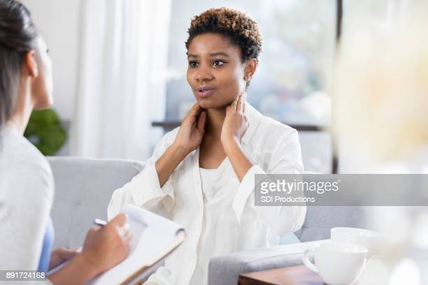 female patient describes symptoms to doctor - throat photos stock photos and pictures