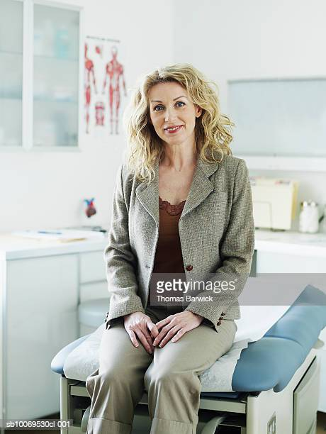 female patient in medical room, smiling, portrait - examination table stock pictures, royalty-free photos & images