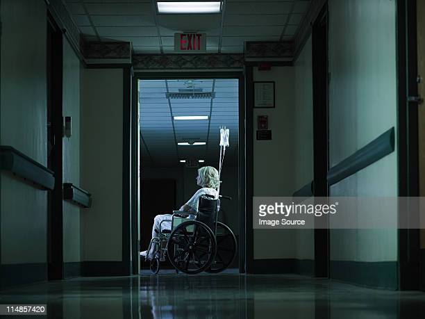female patient in wheelchair with intravenous drip - ominous stock pictures, royalty-free photos & images