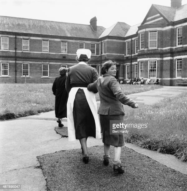 A female patient is led away by a nurse after spending time in the grounds at at the Netherne Mental Hospital near Coulsdon Surrey 1953 Original...